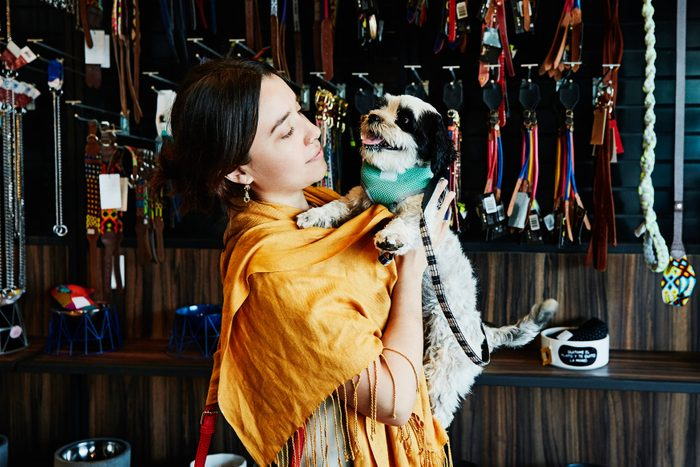 Woman holding pet dog while shopping in pet store