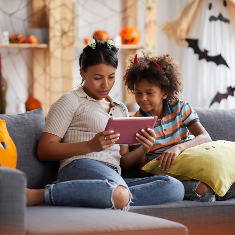 Young attractive black mother sitting on sofa in living room and using tablet while reading Halloween story to son