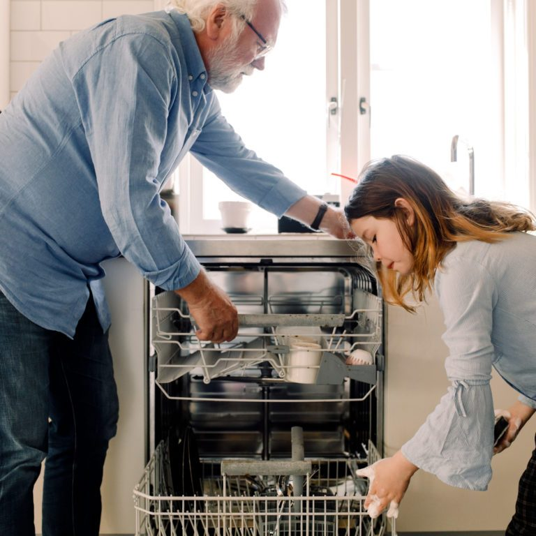 Grandfather assisting granddaughter in cleaning dishwasher at kitchen