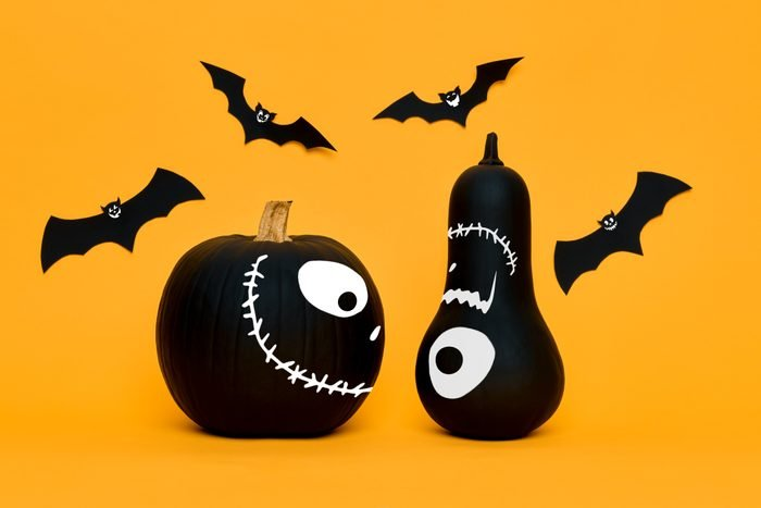 Cute Halloween pumpkins with funny smiling faces and paper bats flying over orange background. Halloween concept.