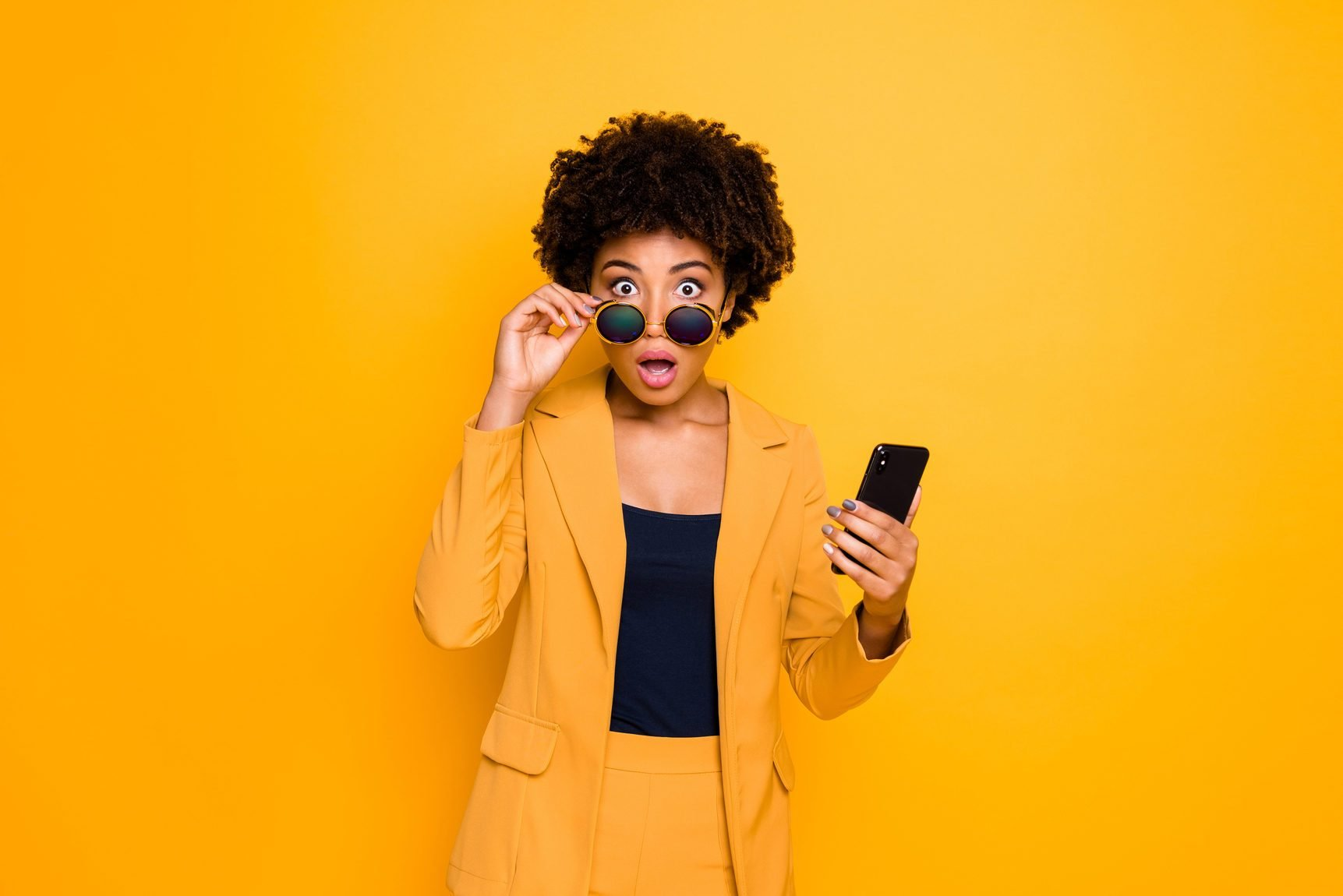 Portrait of shocked afro american girl use smartphone read news on social network account get notification about dislike scream omg wear stylish fashionable clothes isolated yellow color background