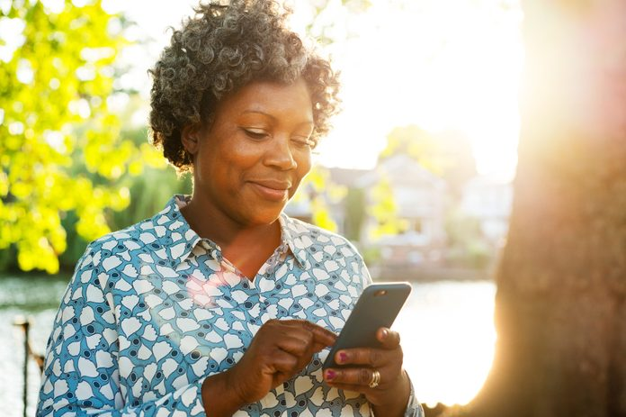 Smiling woman with smart phone outside