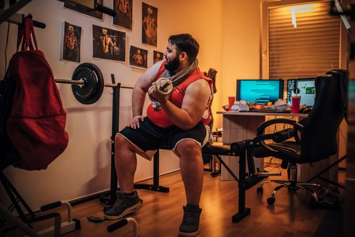 Large build man training with weights at home