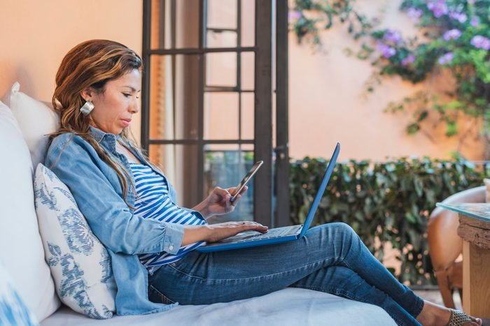Woman using laptop and mobile phone on outdoor veranda