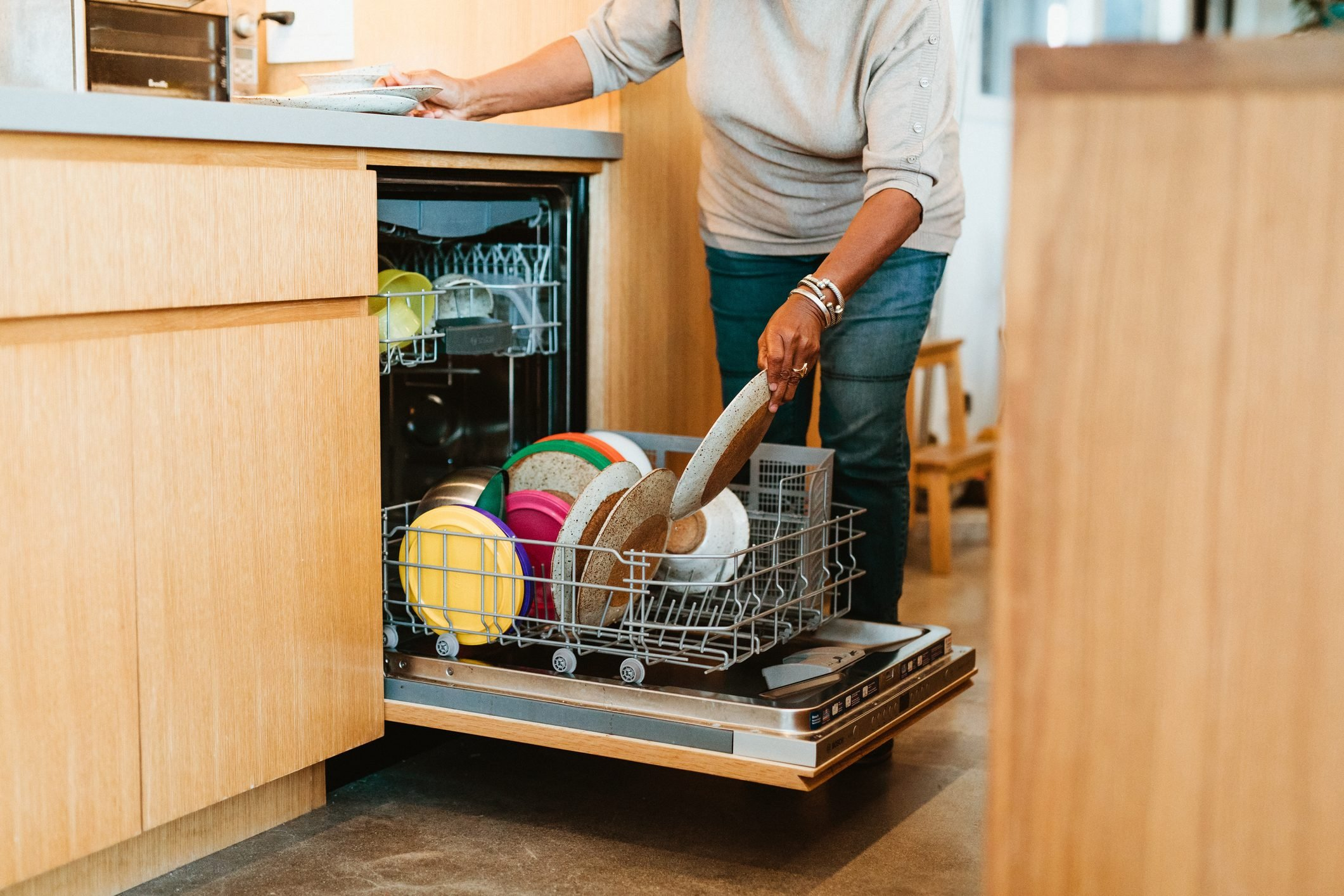 Senior woman keeping plates in dishwasher at home
