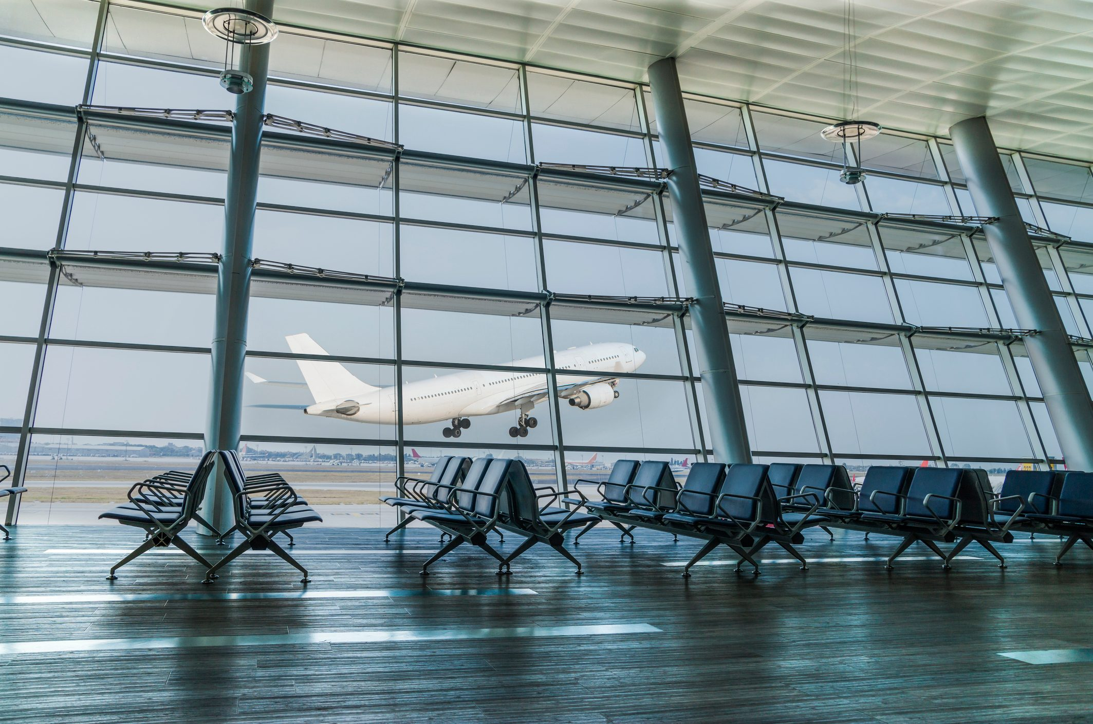 Empty airport departure lounge and airplane take off