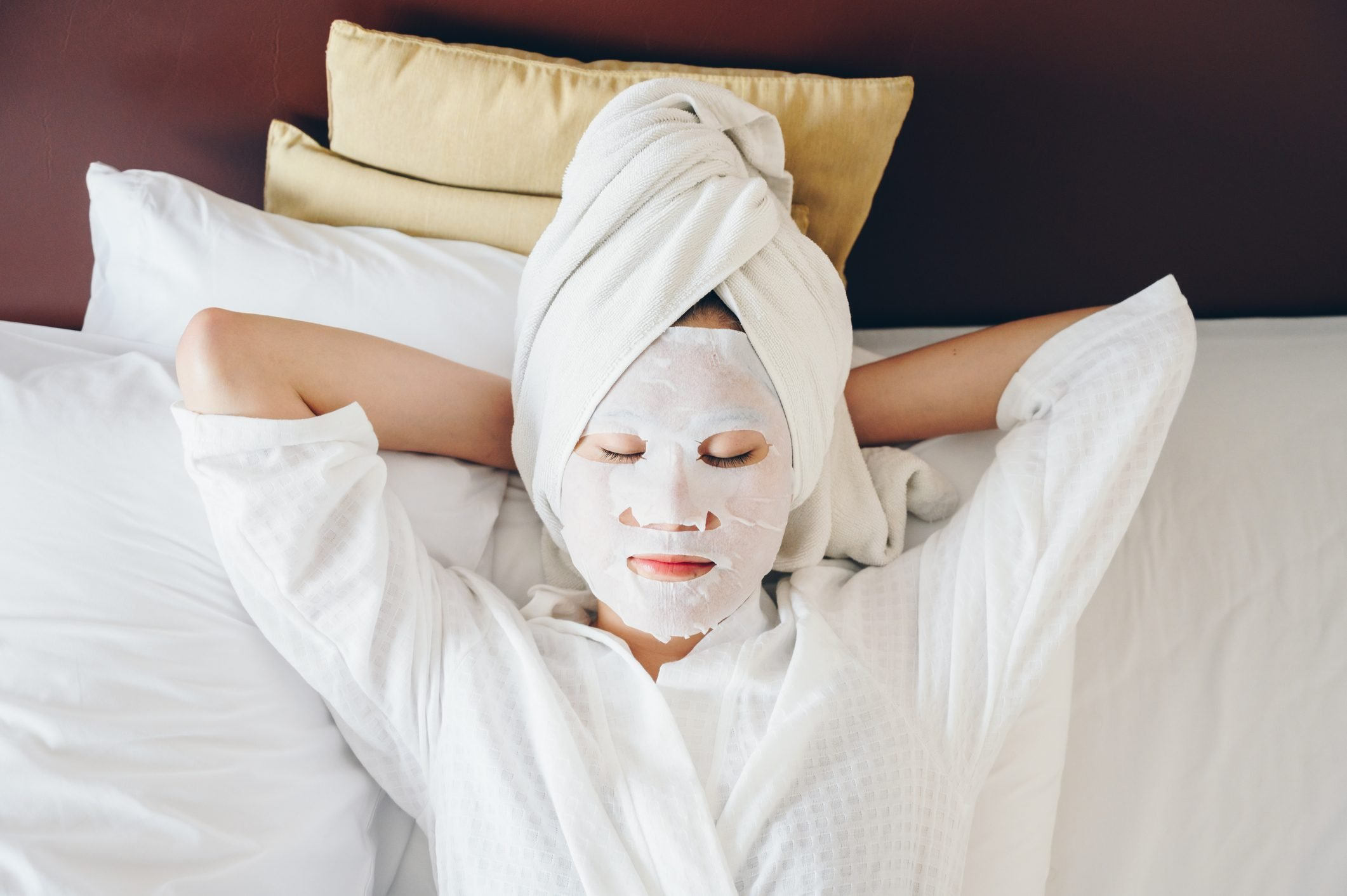 Portrait of young woman sleeping on bed with applying facial mask for enhance her skin.