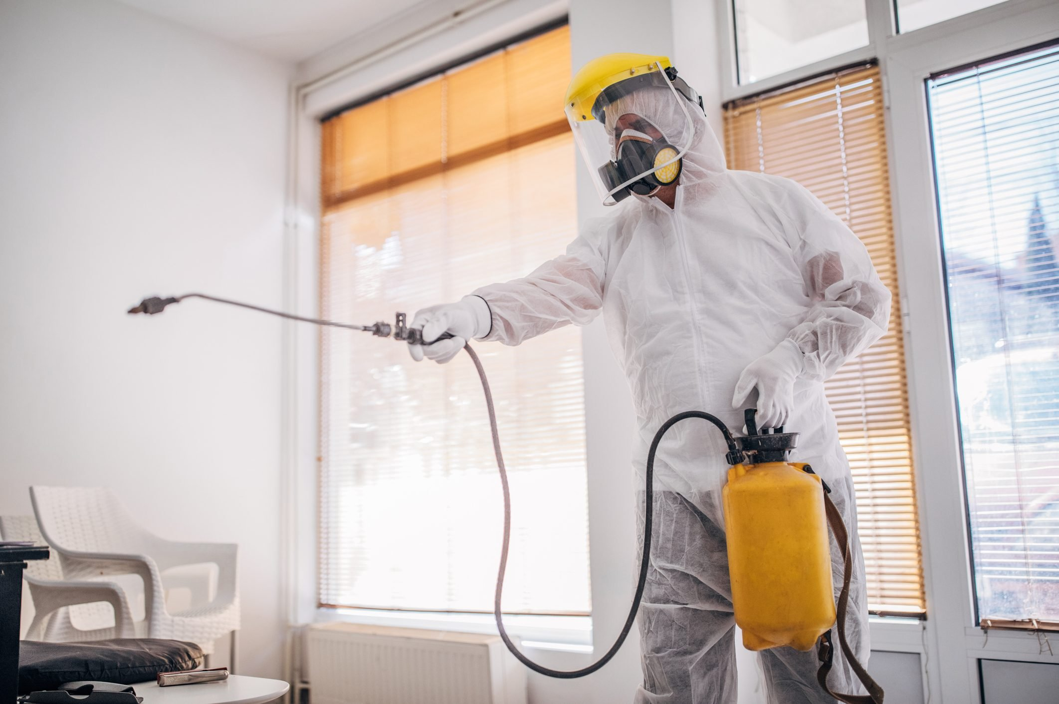 Man in protective suit disinfecting and spraying every room in the building