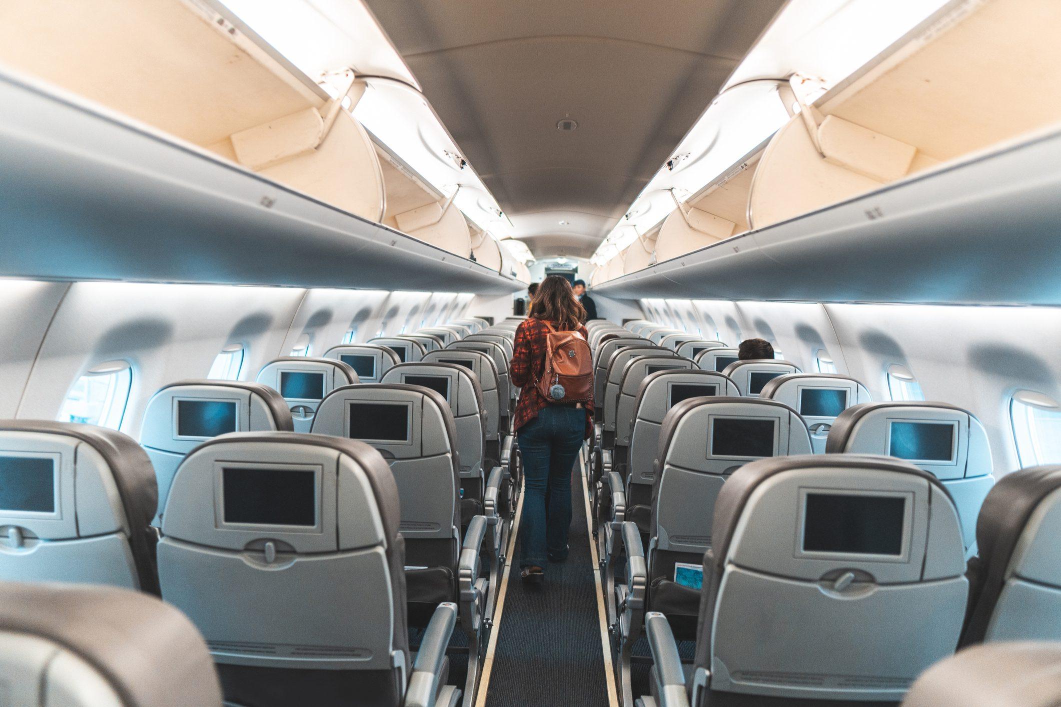 Woman walking the aisle on plane
