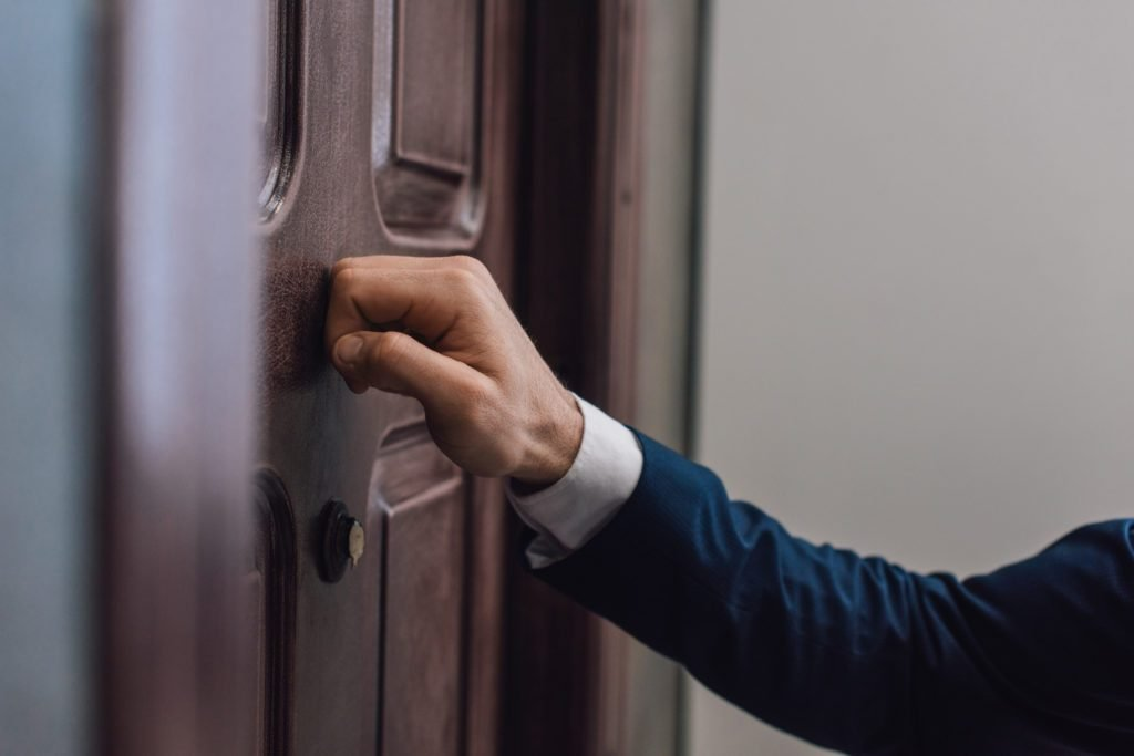 Cropped view of collector knocking on door with hand