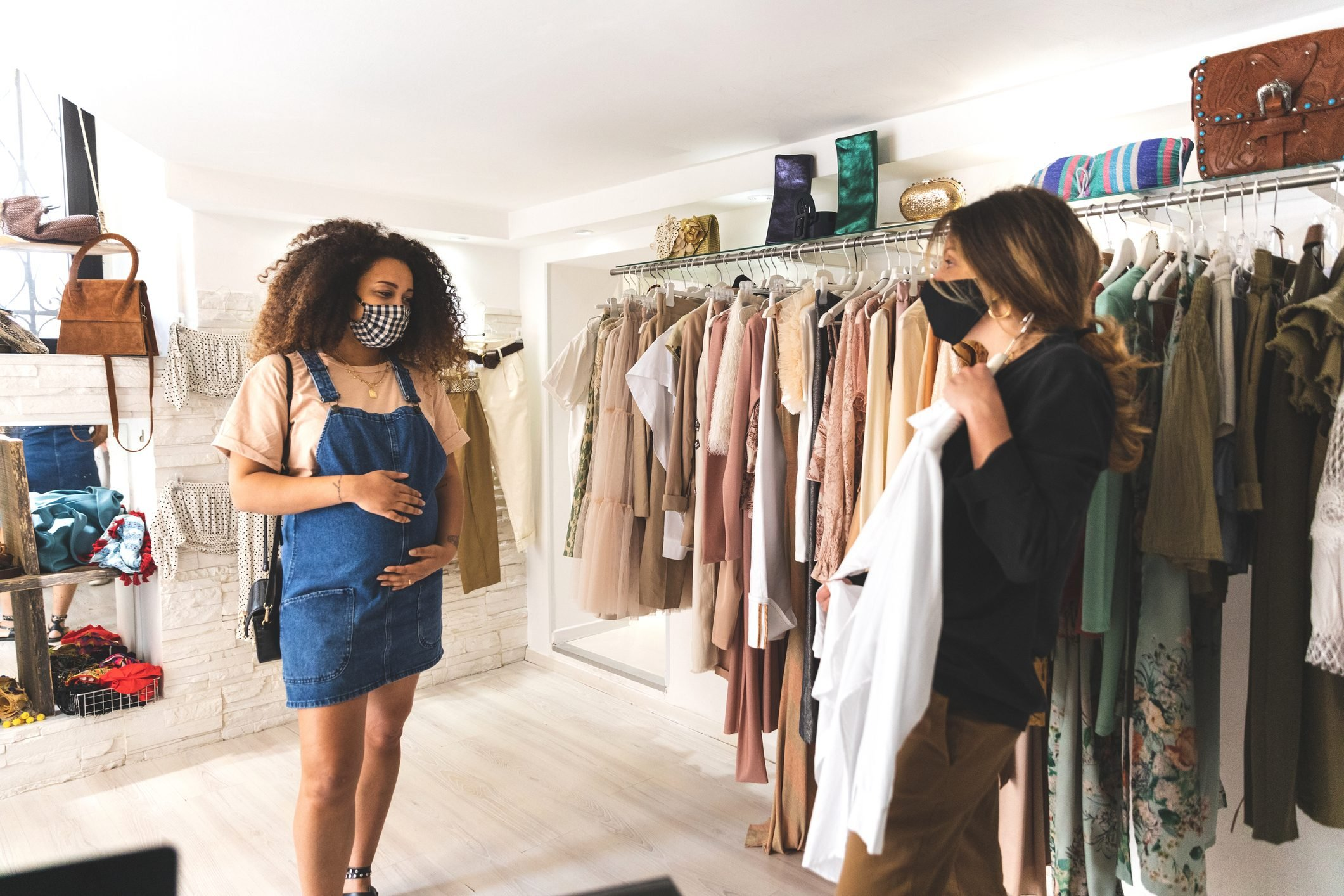 Shop owner showing new clothes collection to a customer