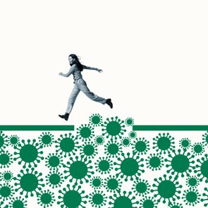 Woman jumping over green coronavirus under ramp