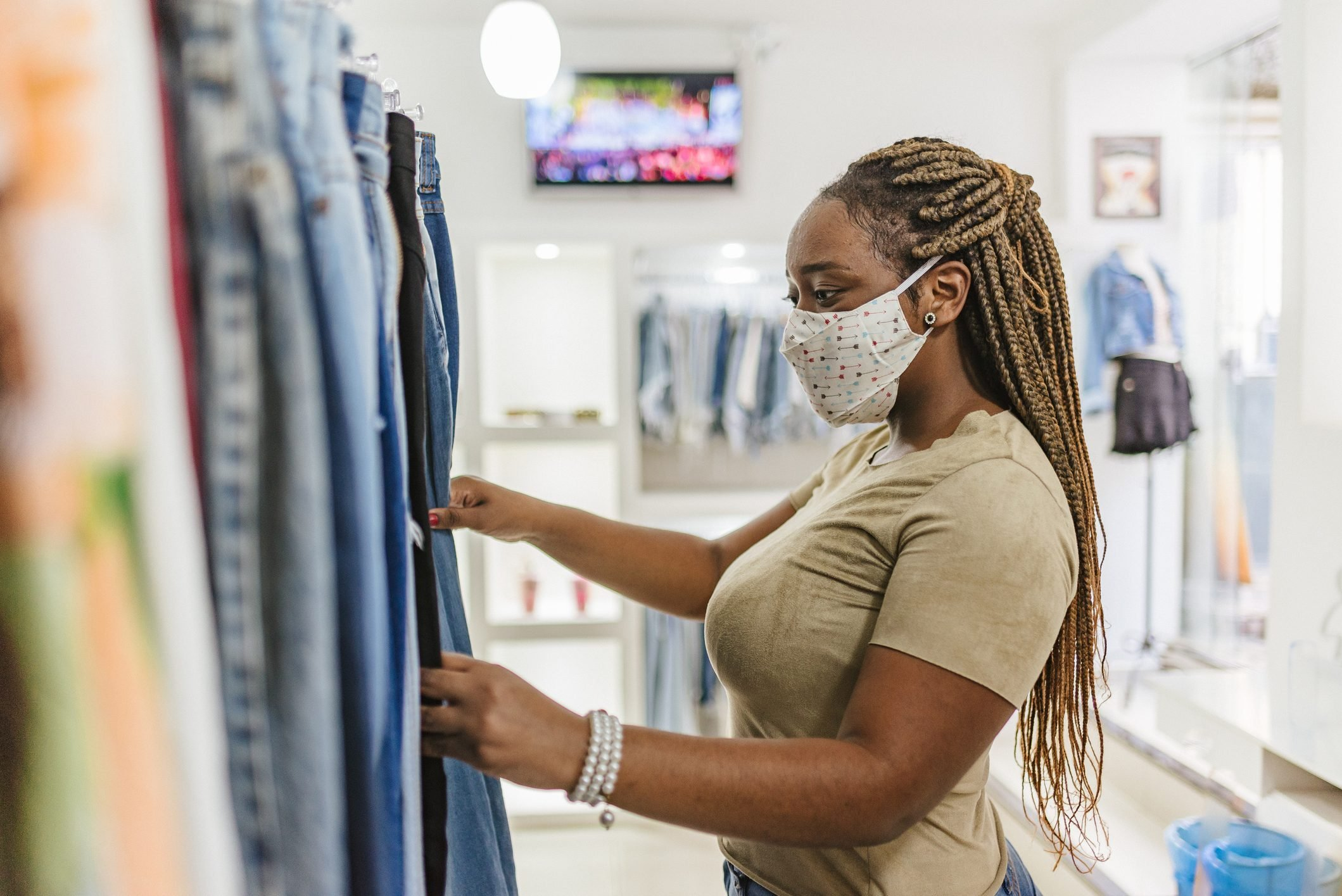 Covid-19: Woman customer choosing clothes at the mall store
