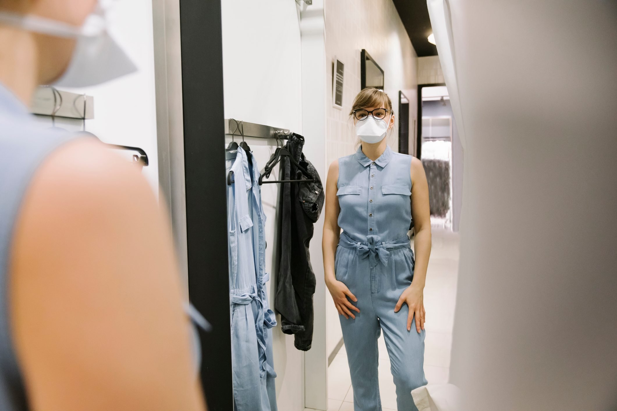 Woman with face mask trying on clothes in a fashion store