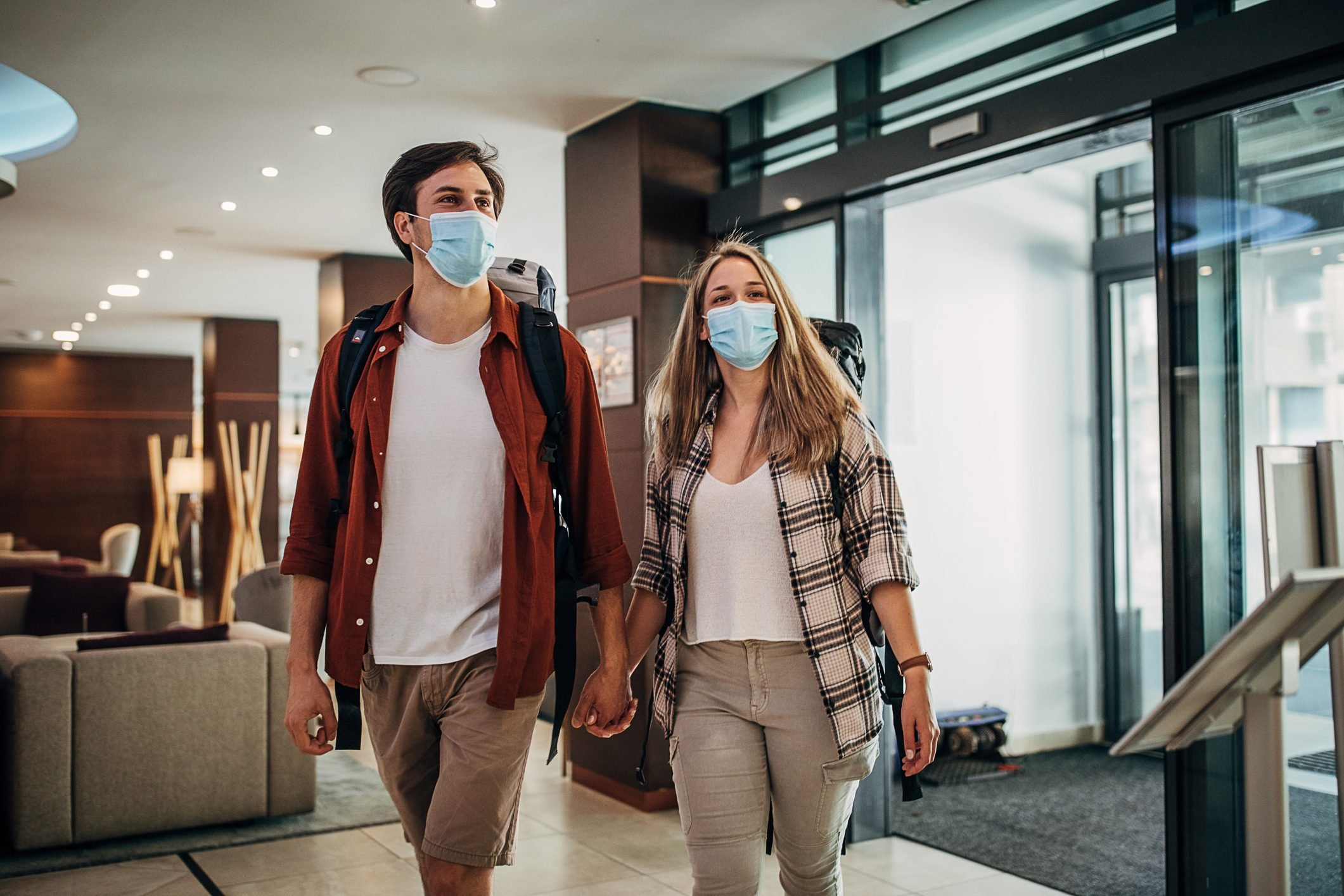 One young couple with protective face masks entering the hotel lobby