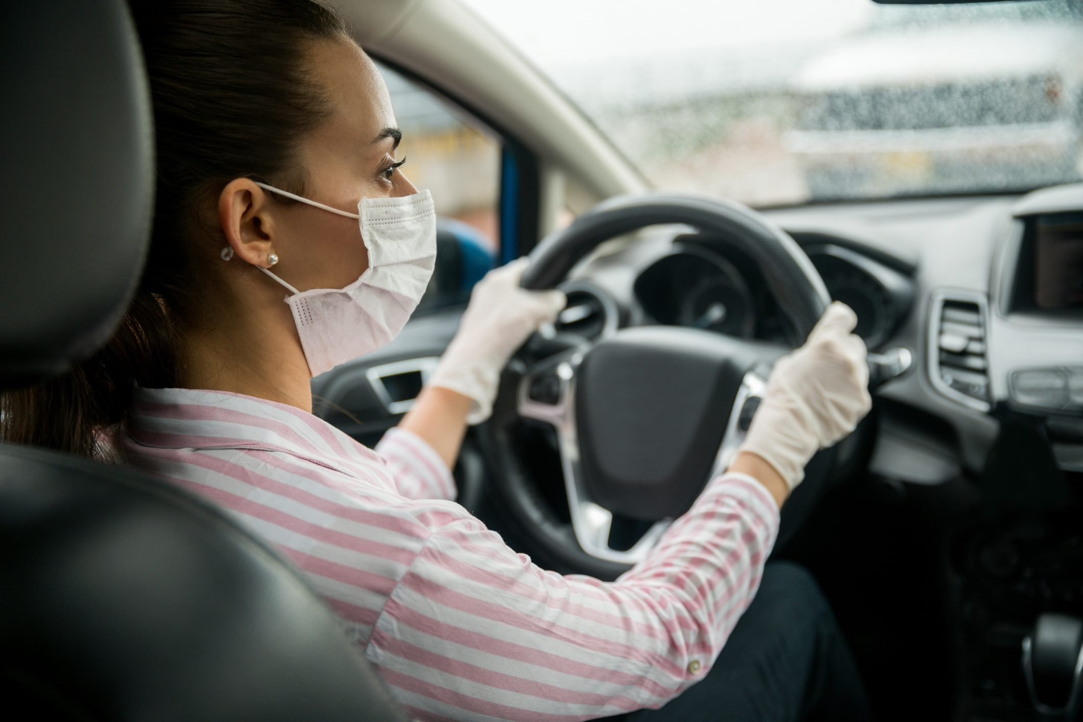 Female driver wearing a facemask and gloves in the car