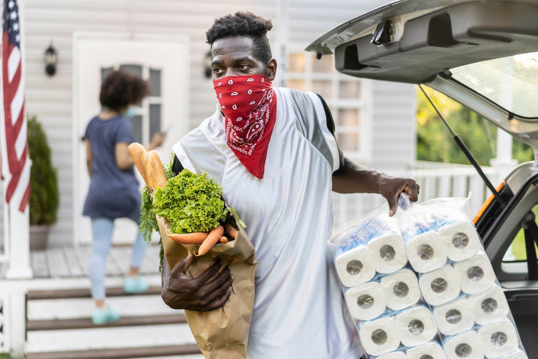 man wearing bandana as face mask carrying groceries