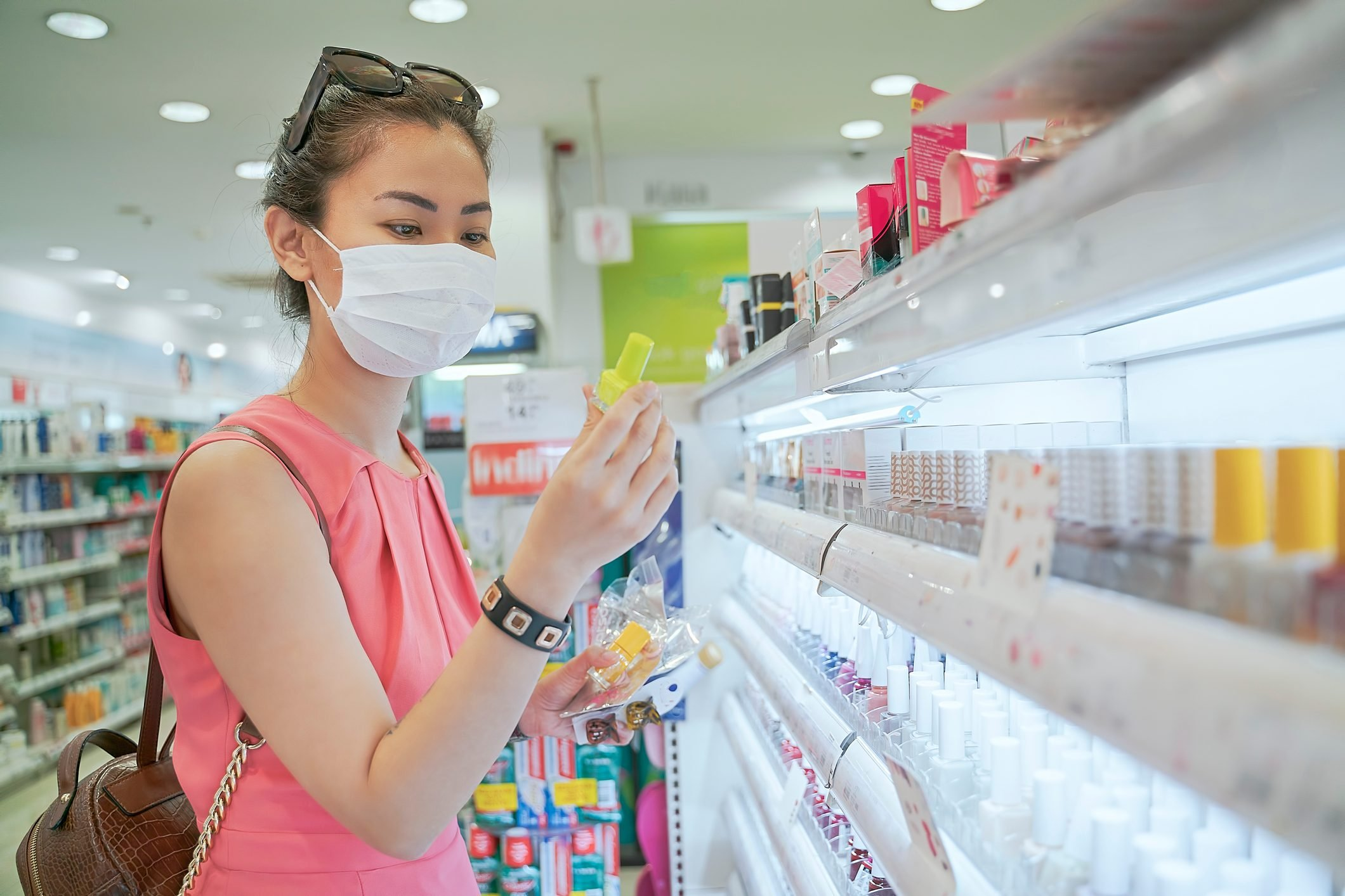 Woman buying nail polish beauty product during pandemic with face mask