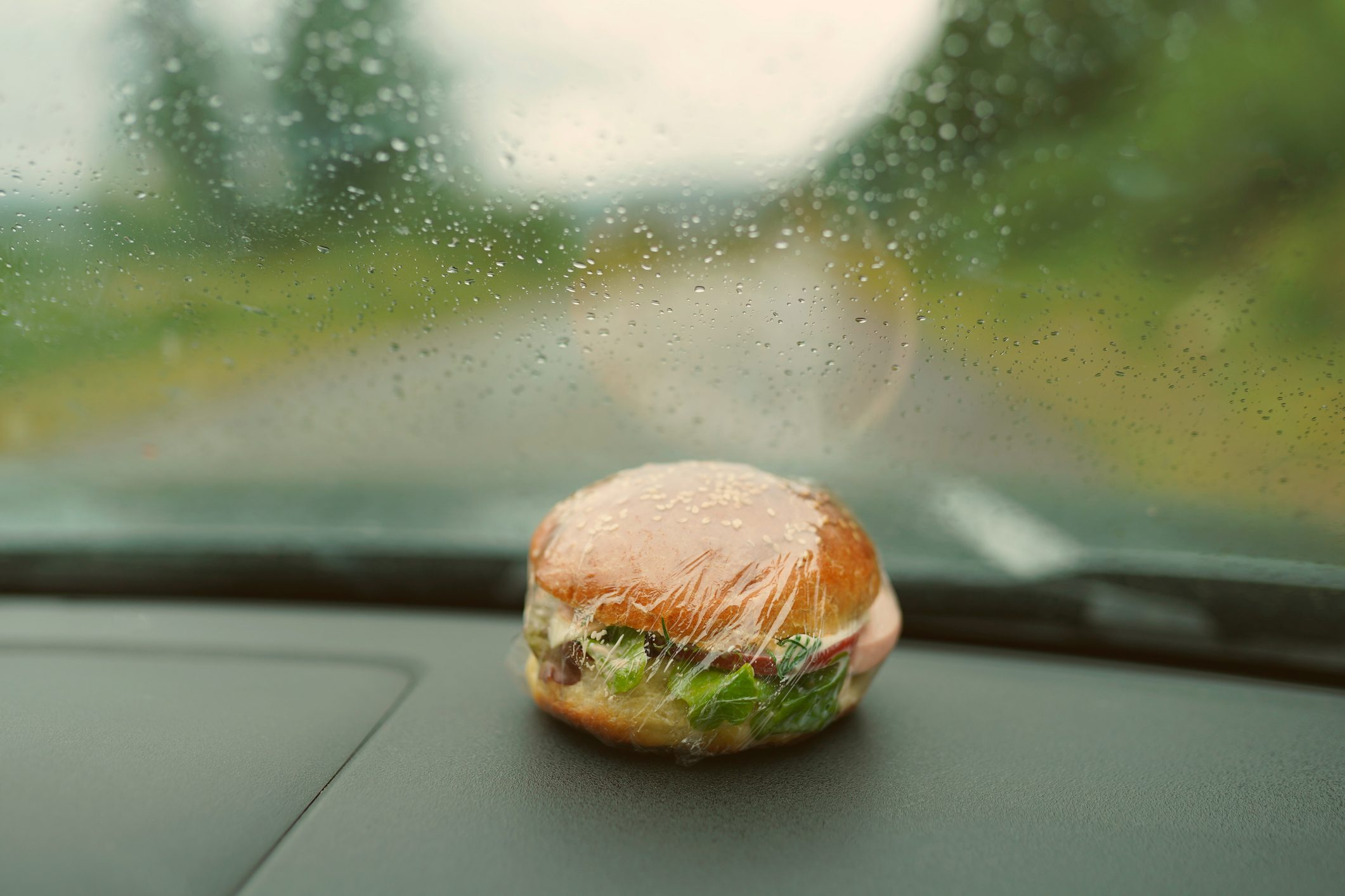 wrapped burger lies on the car dashboard