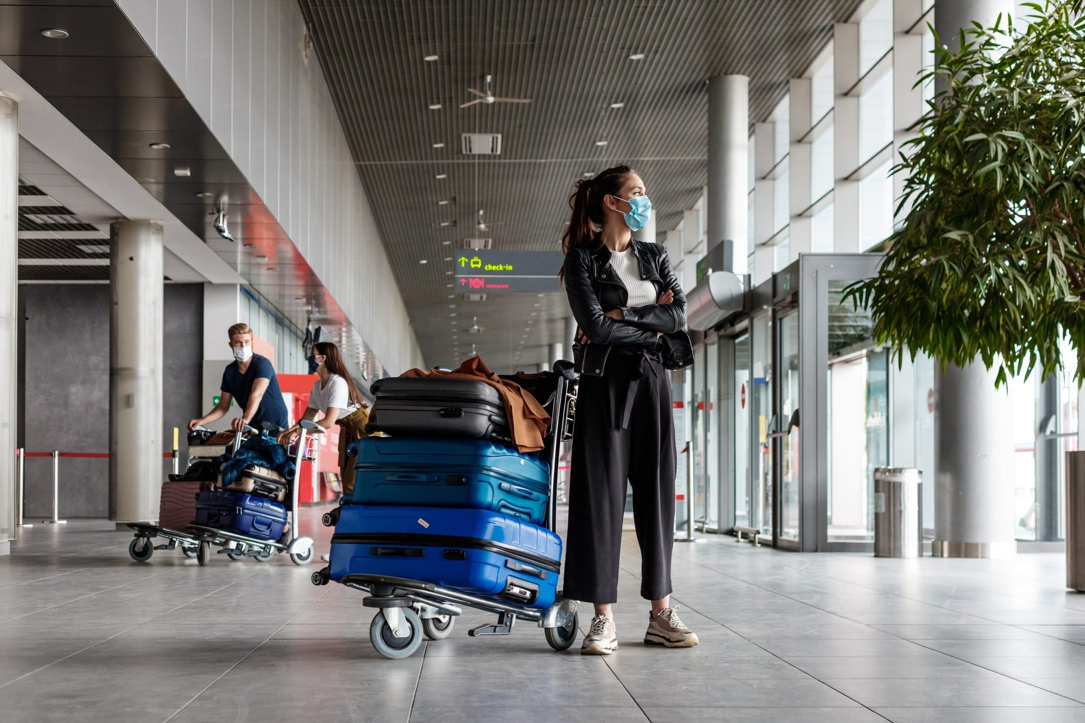 Airtravelers at the airport with luggage, wearing N95 face masks