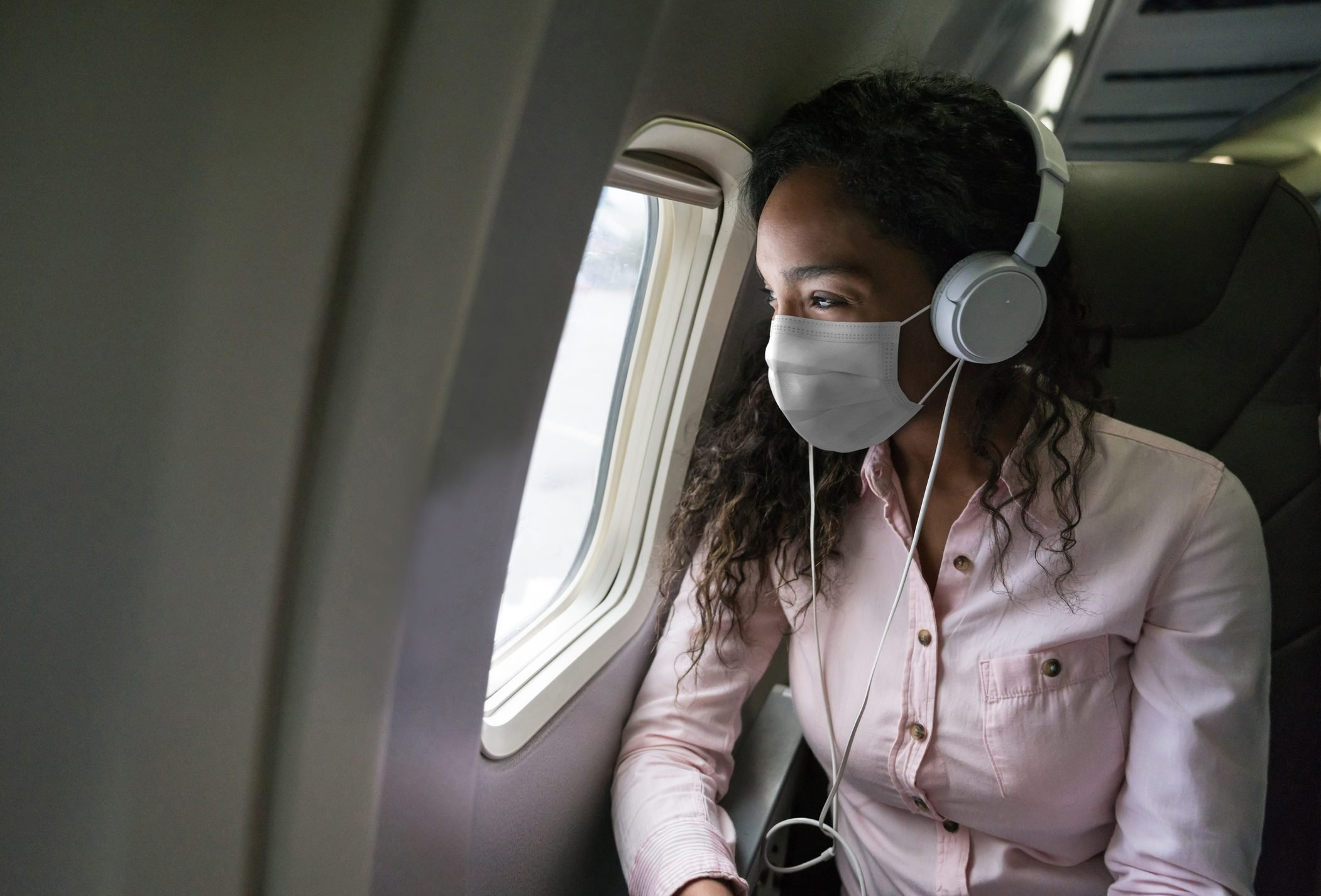 Woman listening to music while flying on an airplane wearing a facemask