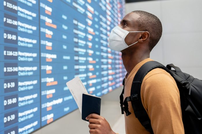 Traveler wearing a facemask at the airport and looking at the flight schedule