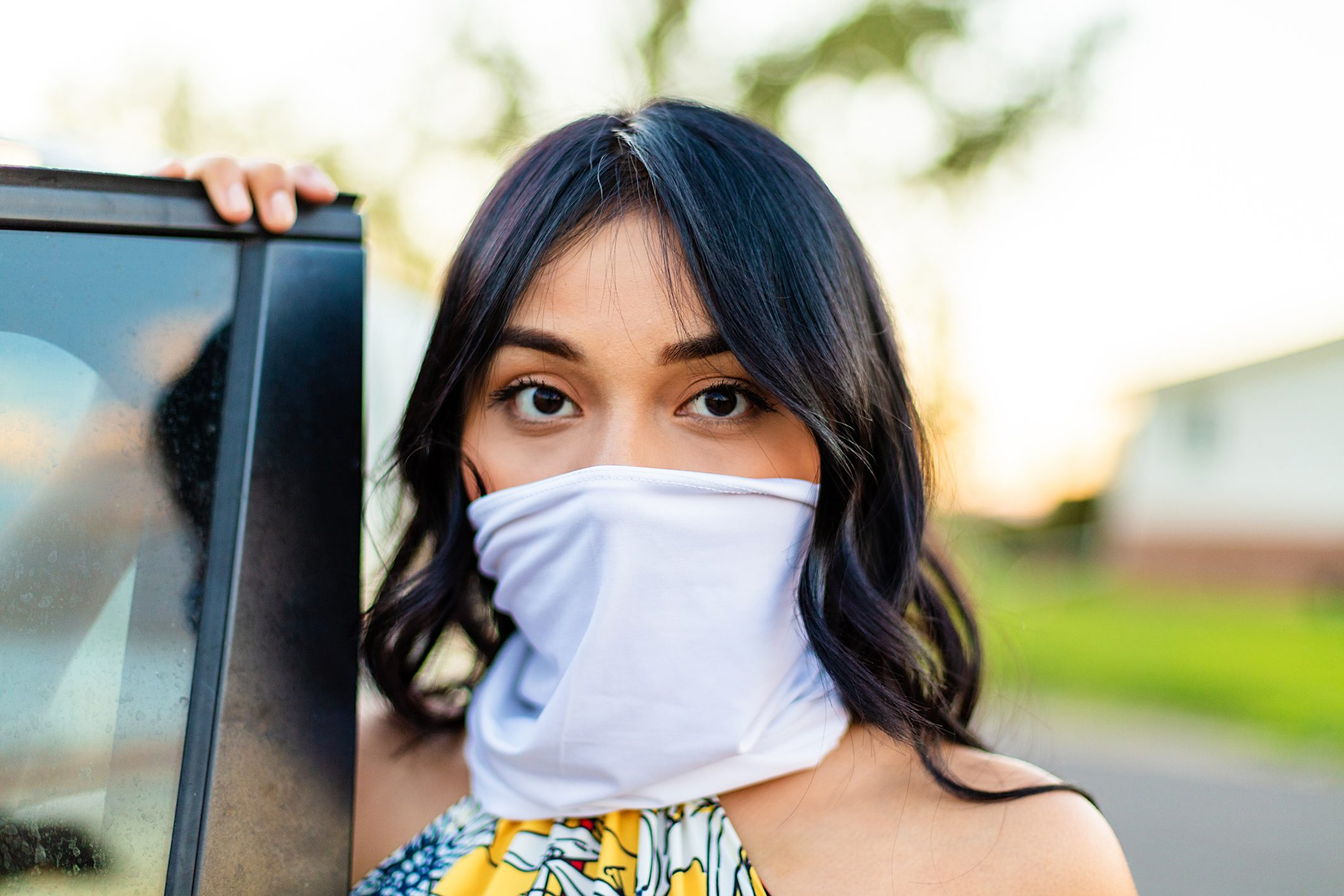 Generation Z Female Next to Automobile with Scarf as Face Mask Covering