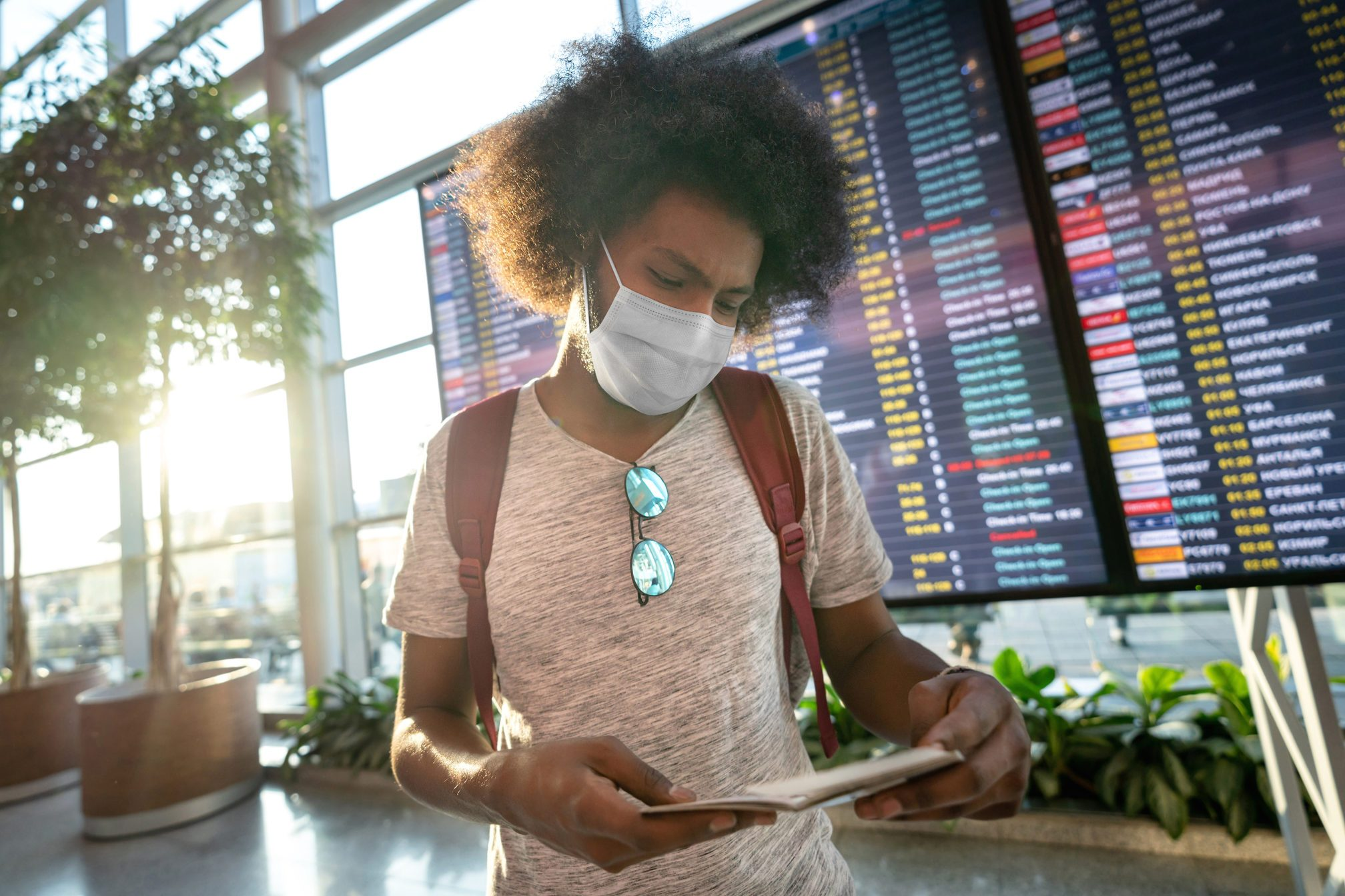 Male traveler wearing a facemask at the airport