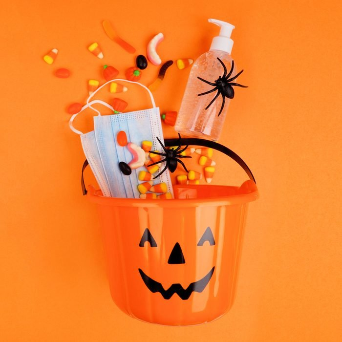 Halloween Jack o Lantern pail with spilling candy and coronavirus prevention supplies. Top view over an orange background.