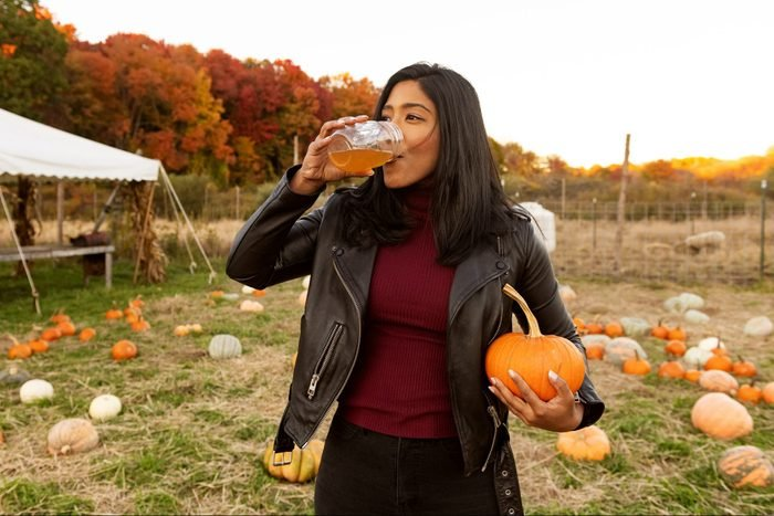 young woman drinking apple cider and holding a pumpkin at the pumpkin patch during autumn