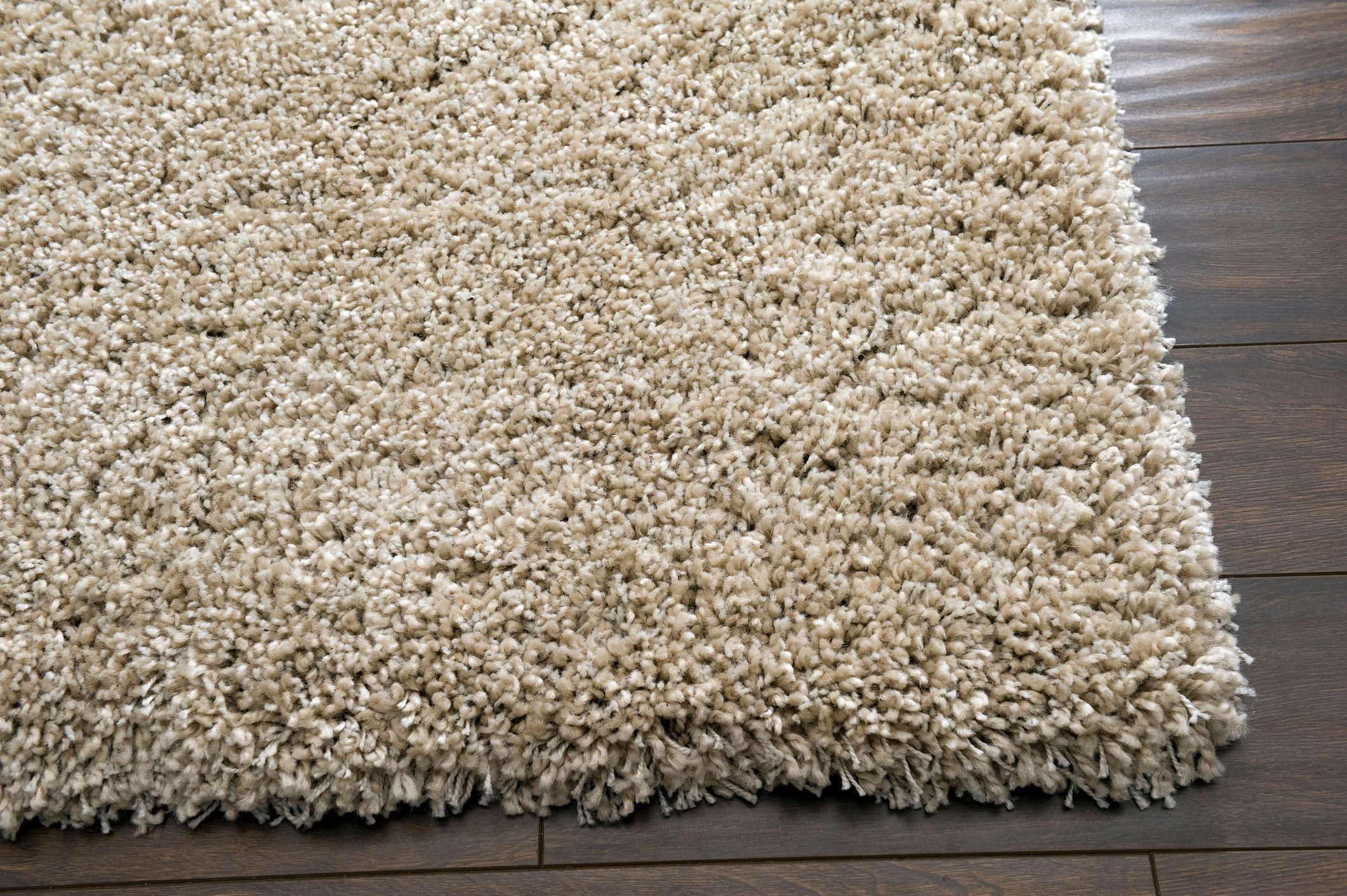 A cream rug on a dark wooden floor