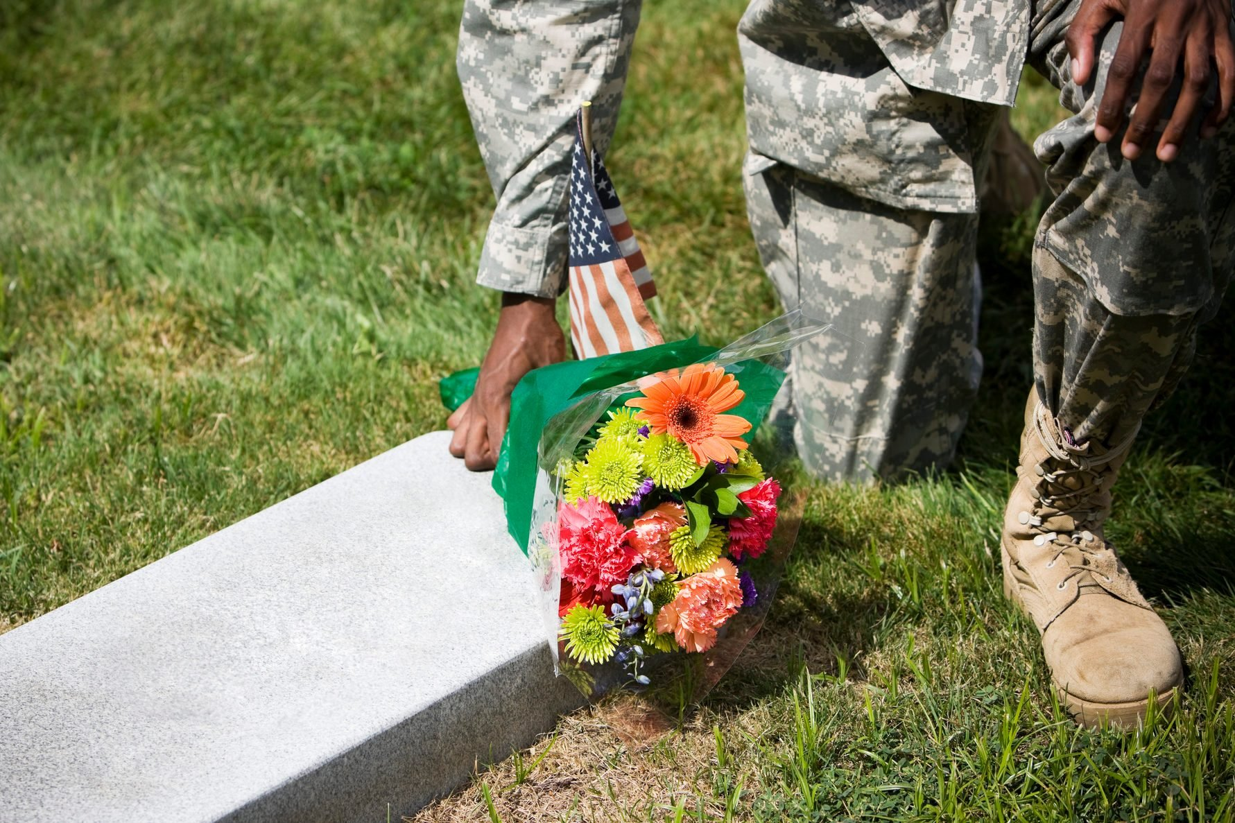 African American Army Soldier Kneeling with Flower Bouquet at Grave