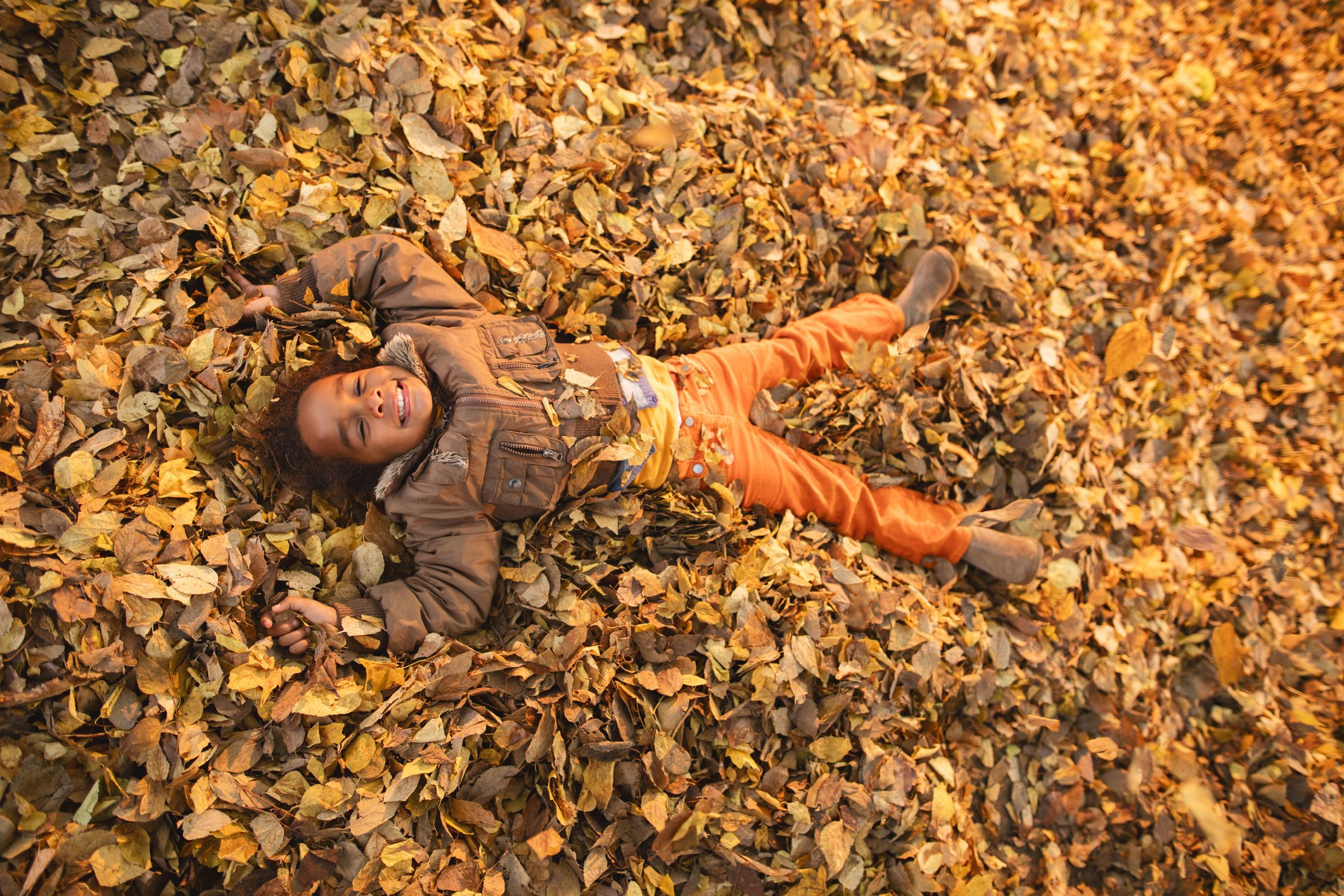 Smiling African American little girl lying among autumn leaves.