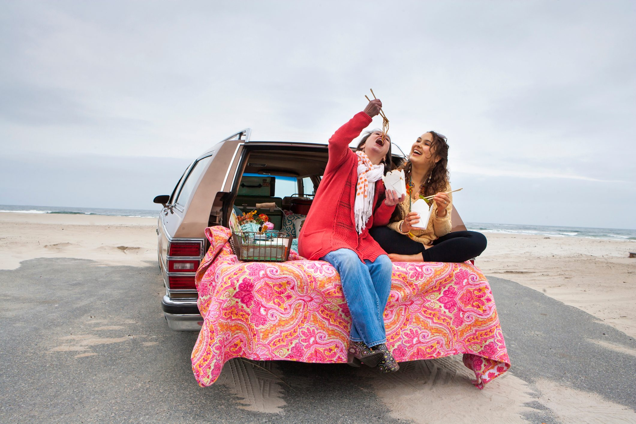 Caucasian mother and daughter eating noodles in car trunk on beach