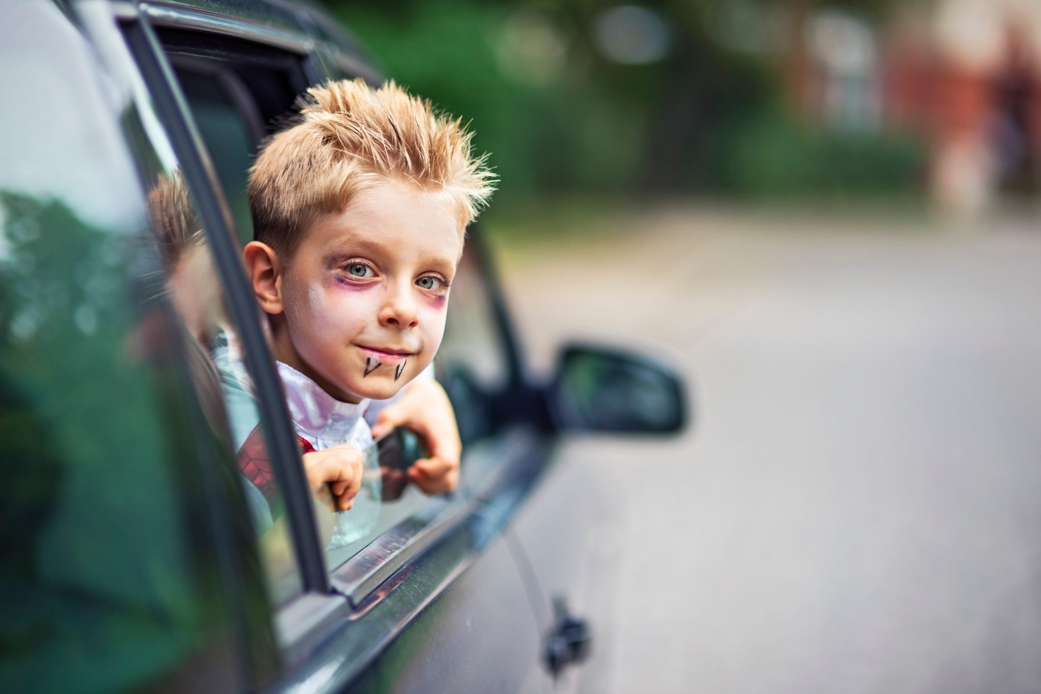 Little halloween boy smiling out of the car