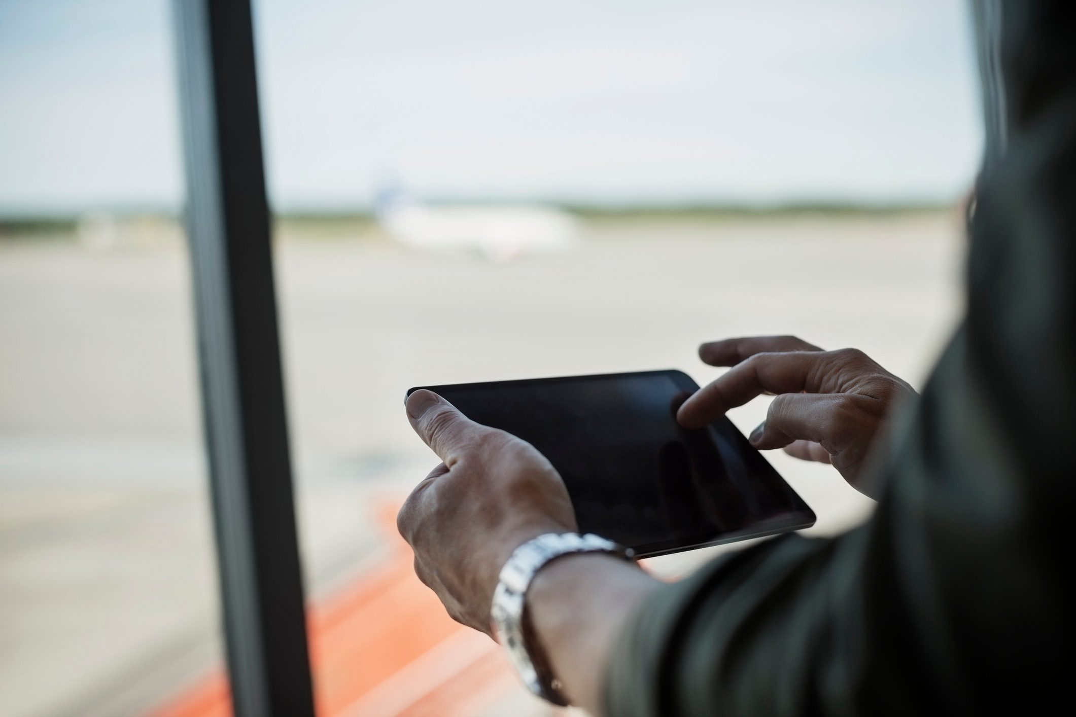 Cropped image of businessman using digital tablet at airport