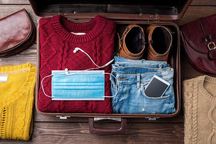 Open suitcase with casual winter clothes and a mask on wooden table.