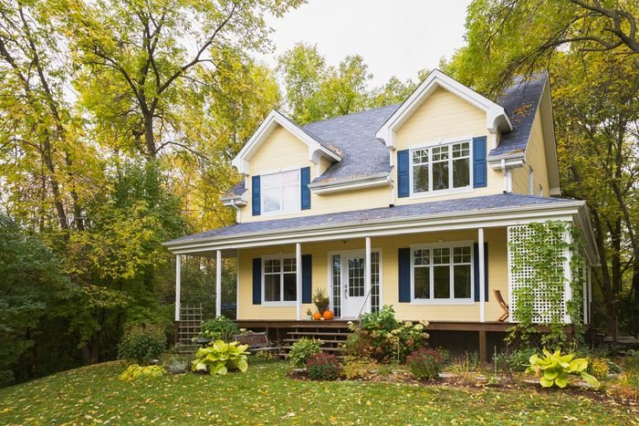 Yellow clapboard with blue and white trim cottage style home facade in autumn, Quebec, Canada
