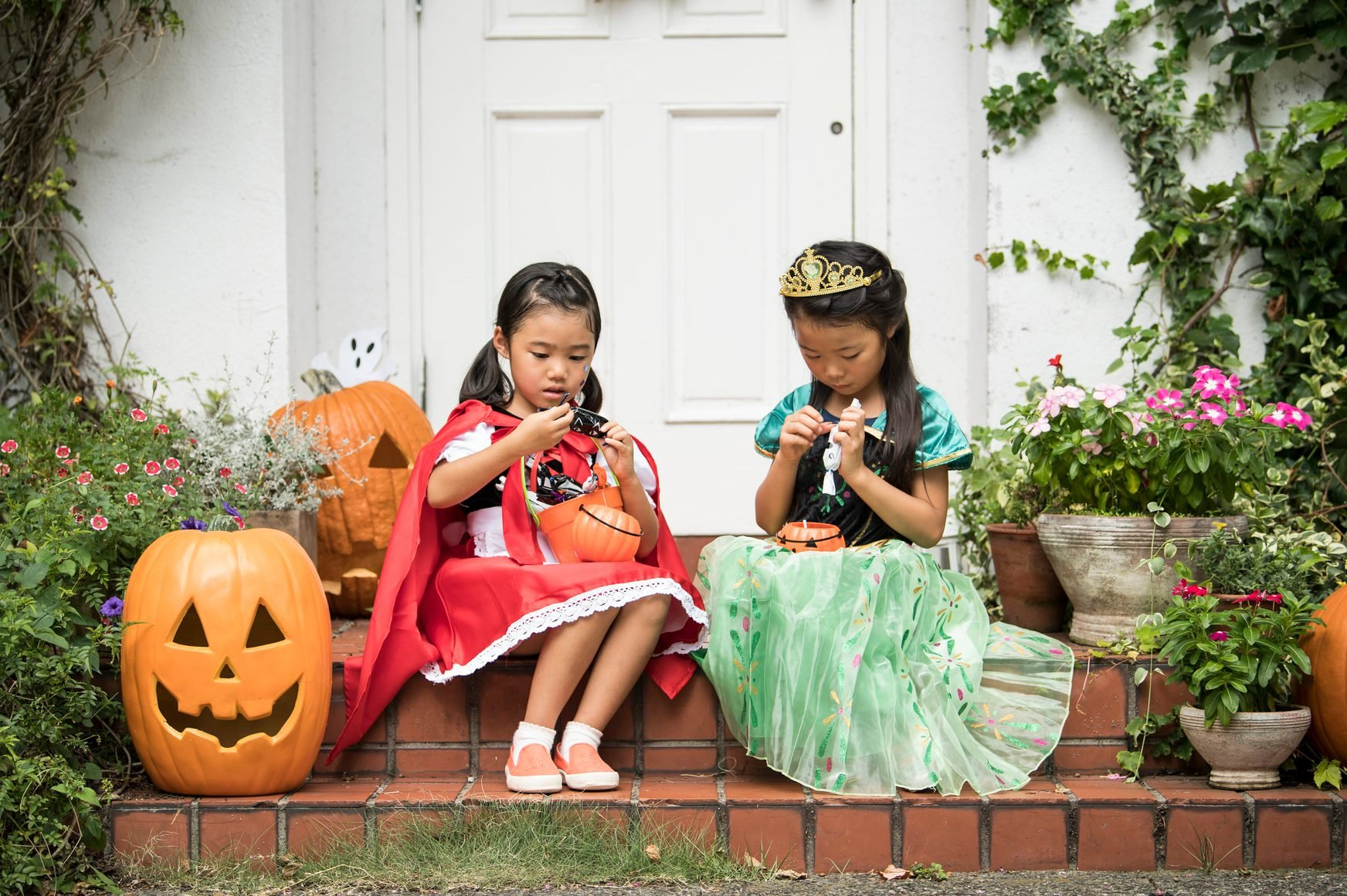 Sitting in front of the house girls are eating sweets.