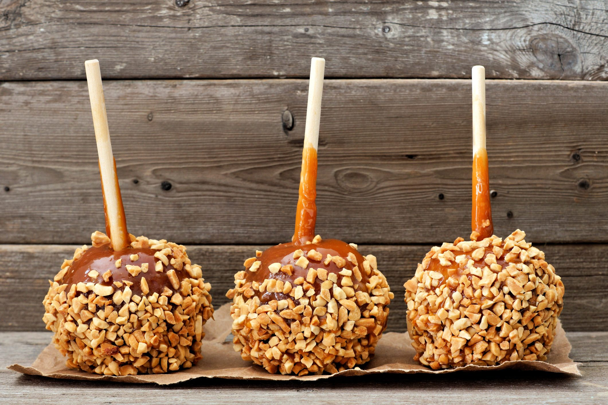 Three caramel apples with nuts against rustic wood