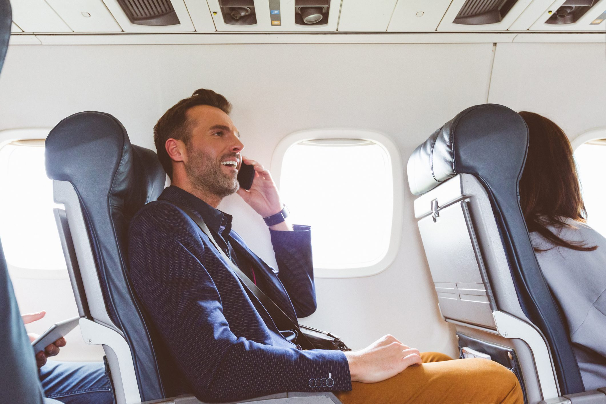Businessman using mobile phone in airplane