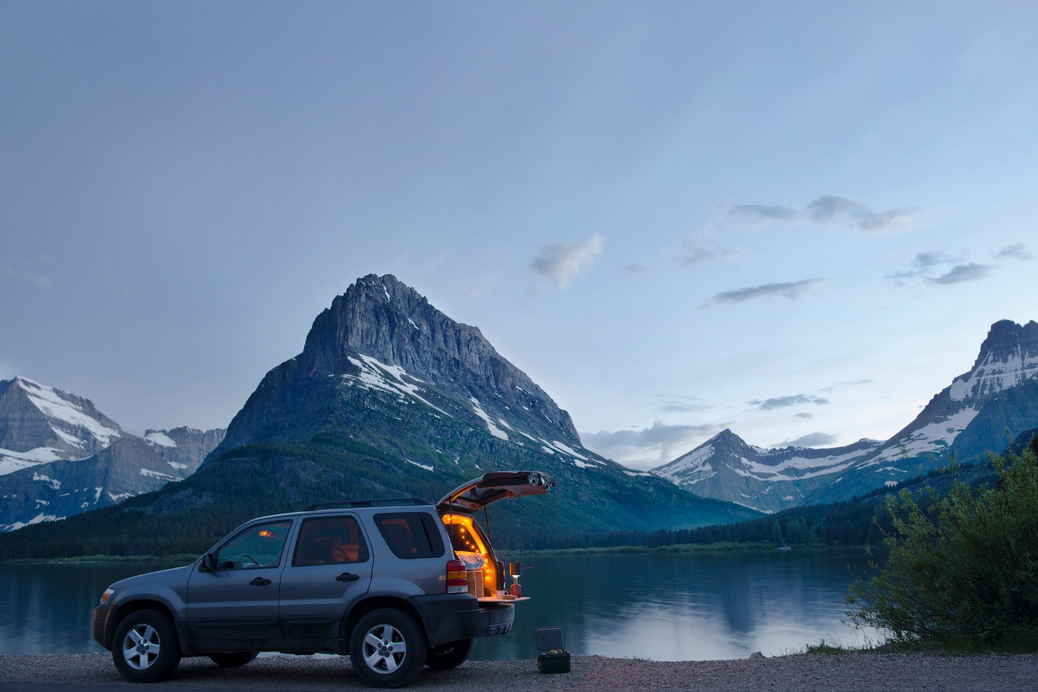 Sports utility vehicle parked on shore of Swiftcurrent lake against Mt. Grinnell