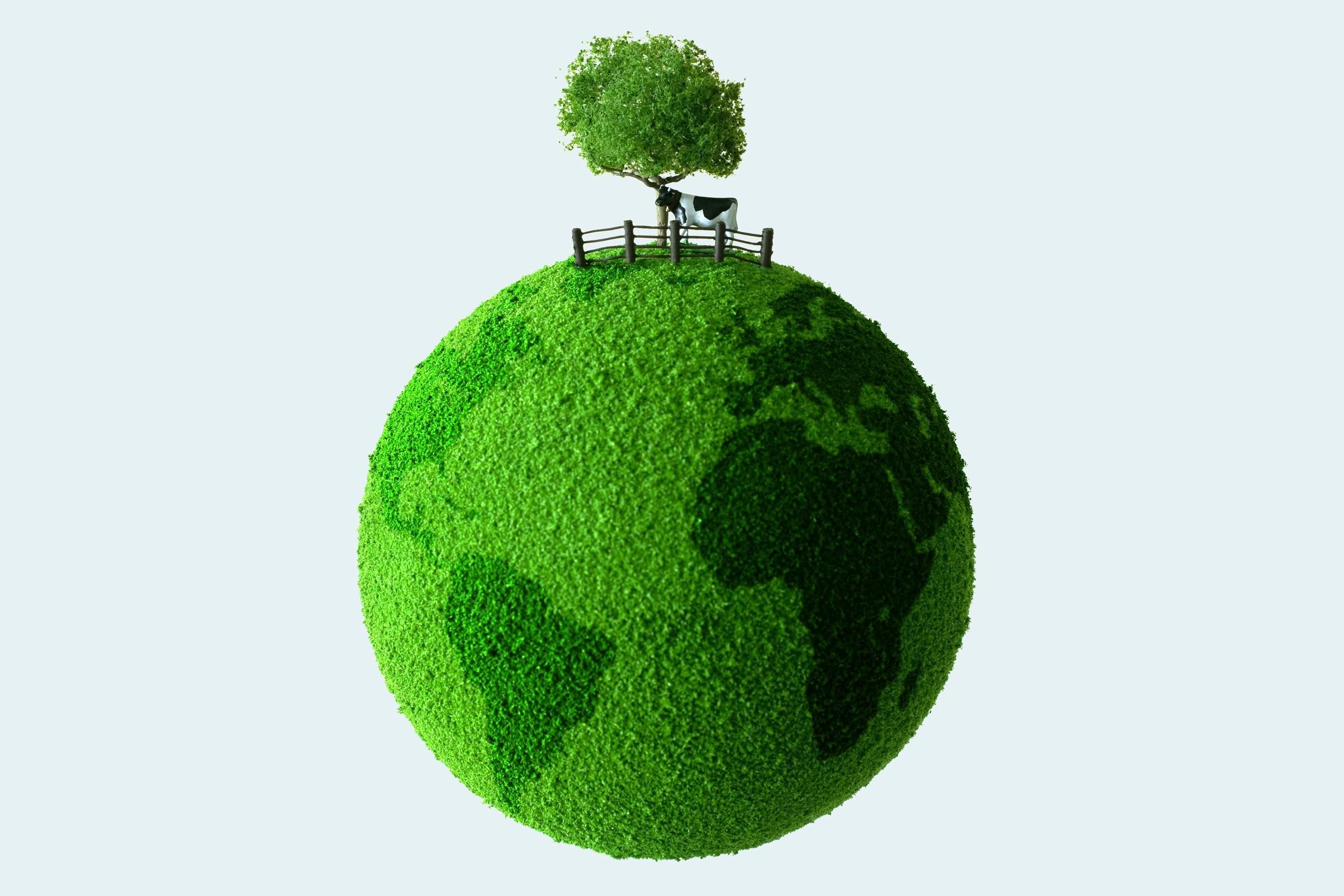 green planet with toy cow and tree on top