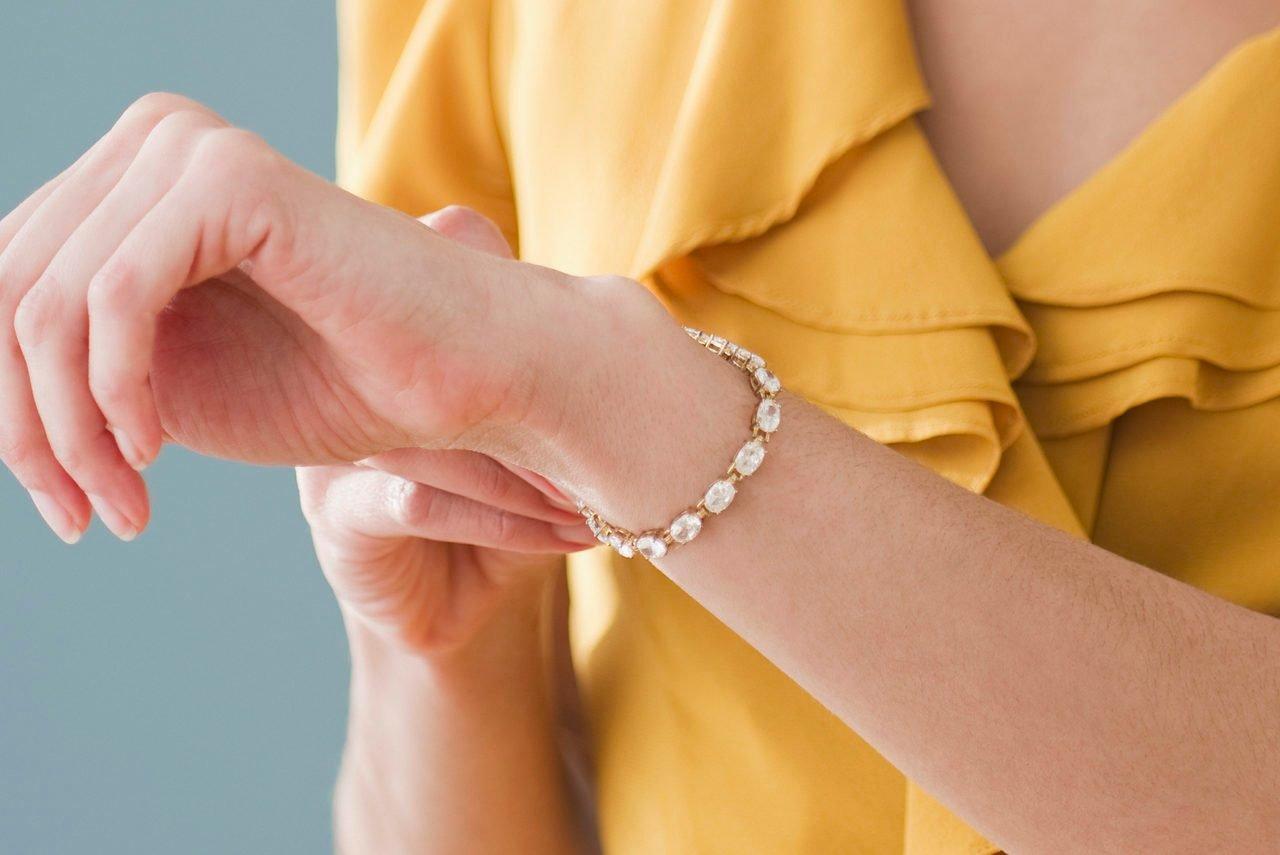 Mixed race woman putting on bracelet