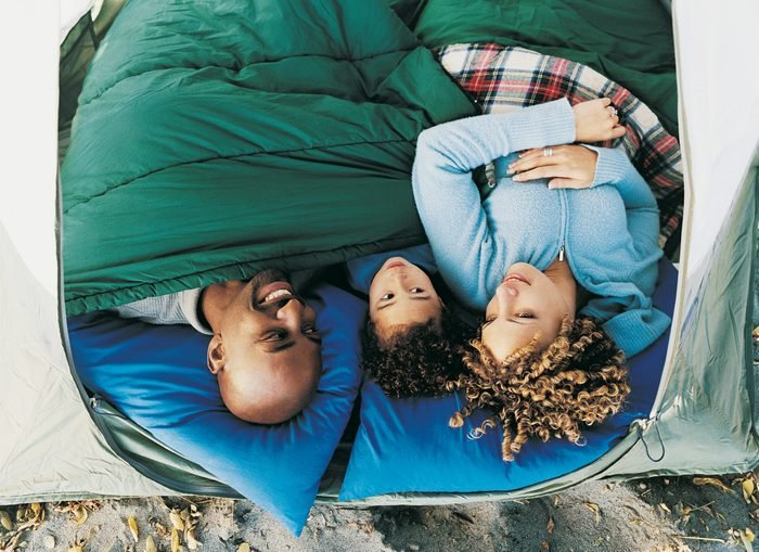 Elevated View of Family of Three Lying in a Tent