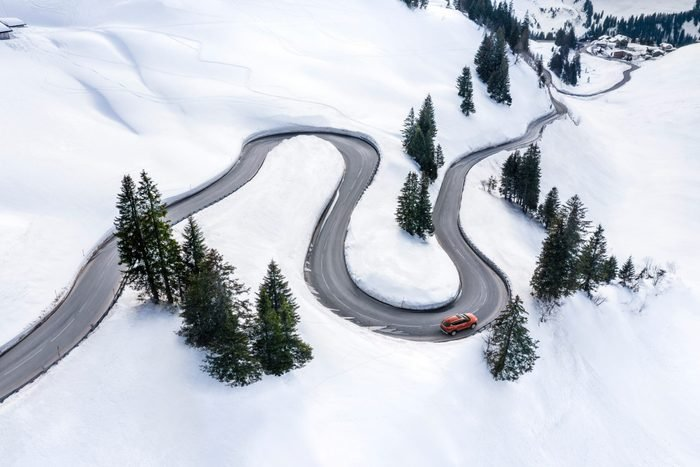 Aerial view of a red car driving in a snowy wilderness landscape
