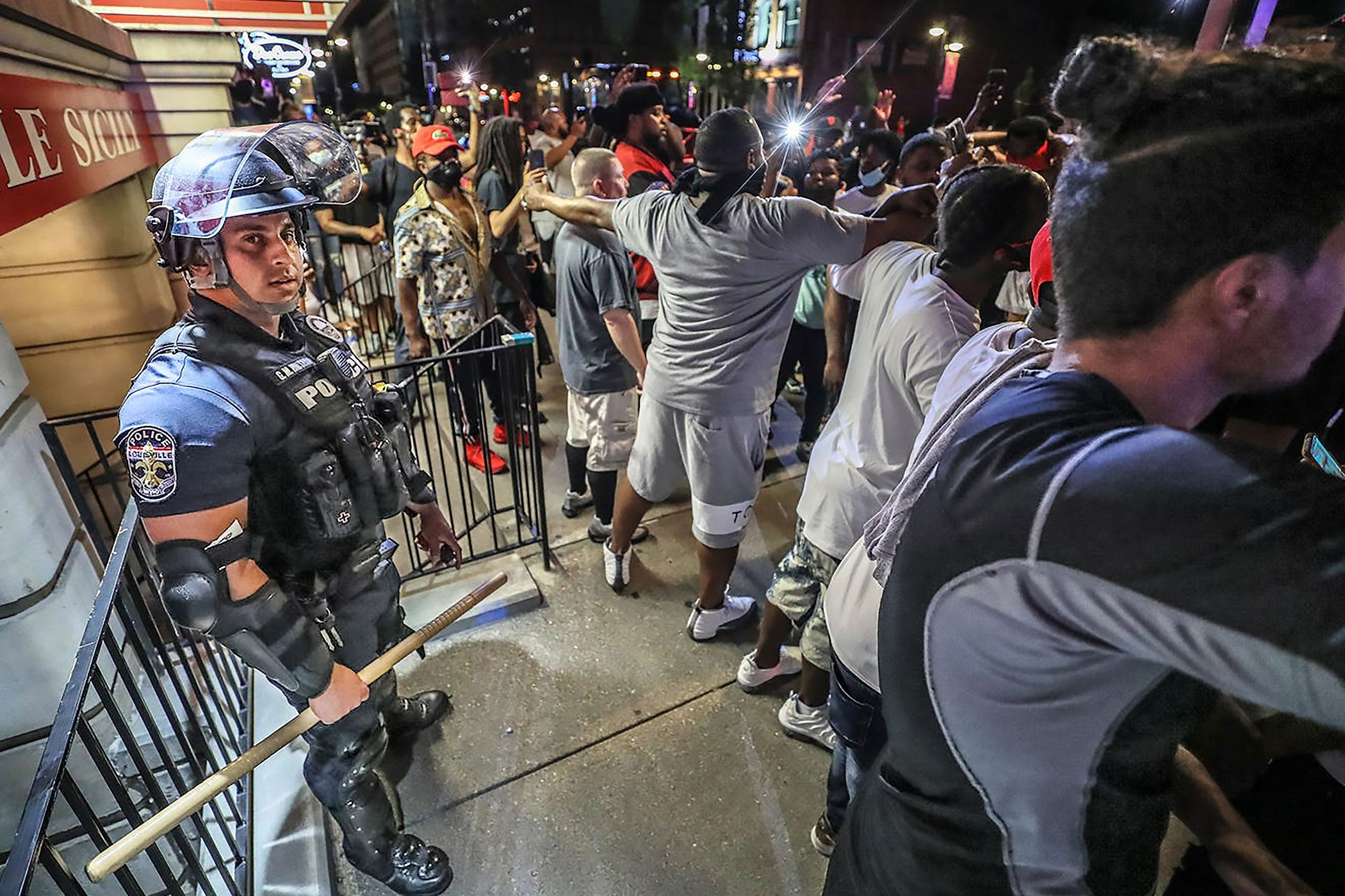 protestors link arms to protect police officer Galen Hinshaw
