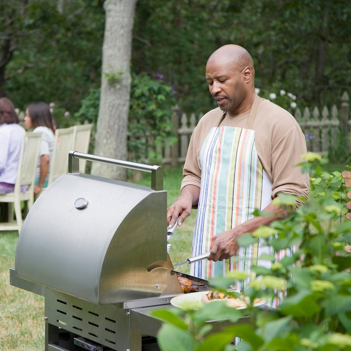 Mature man preparing food on a barbecue grill