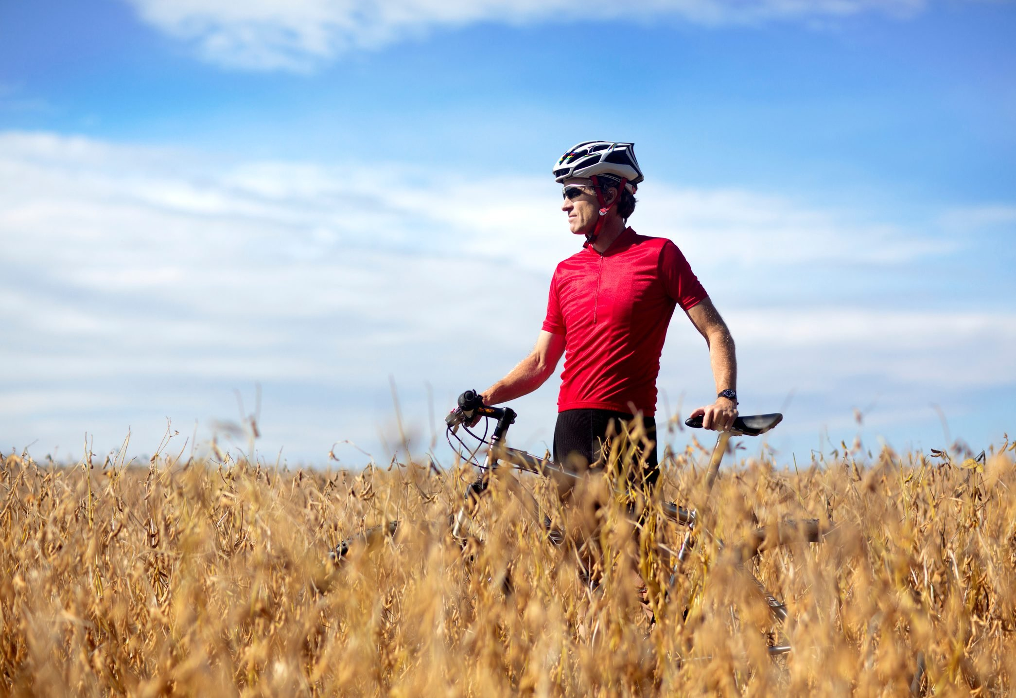 Off road biker stands in a farmer's field