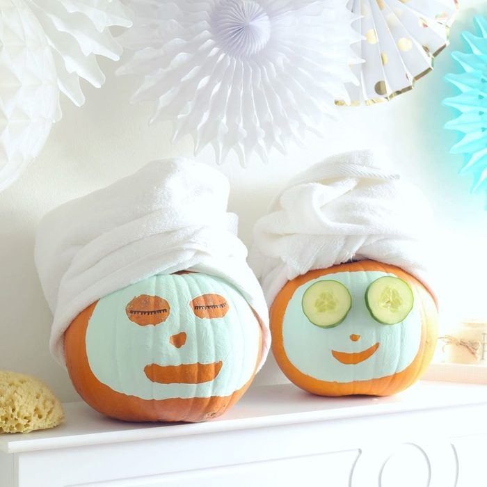"""pumpkins painted to look like they have spa face masks with towels wrapped around their """"heads"""""""